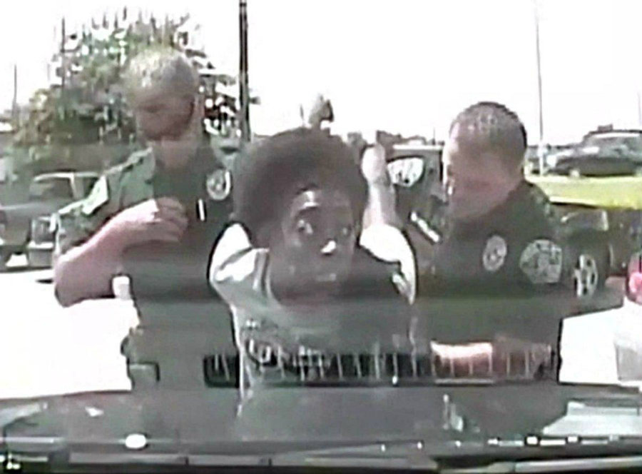 """The woman shouts and resists the officers touch as she asks """"Why are you doing this to me?"""" the officer tries getting King on the ground, as she pulls up. Image Credit: YouTube"""