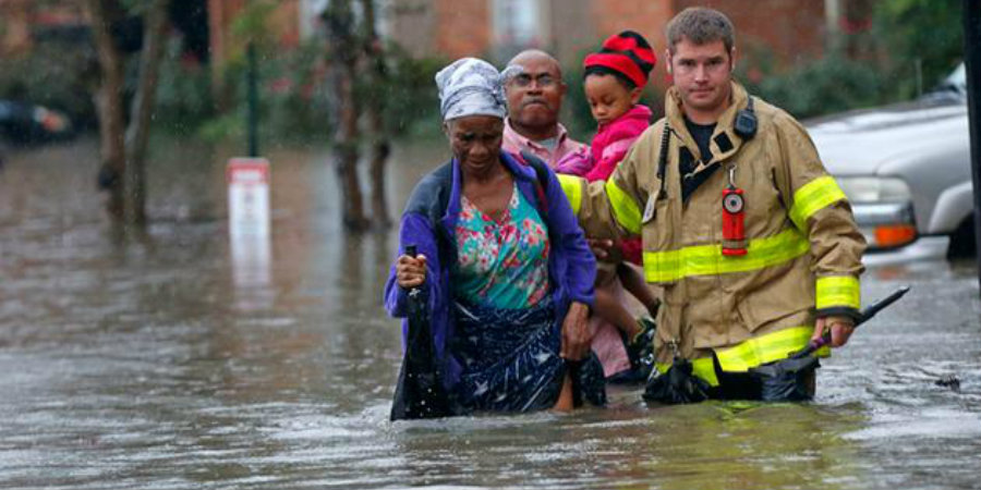 A Louisiana firefighter escorts a family to safety following the community's flood. Image Credit: CBS