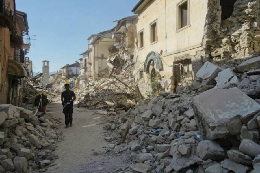 A man walks by plenty of the collapsed buildings after an earthquake hit Italy. Image Credit: NY Times