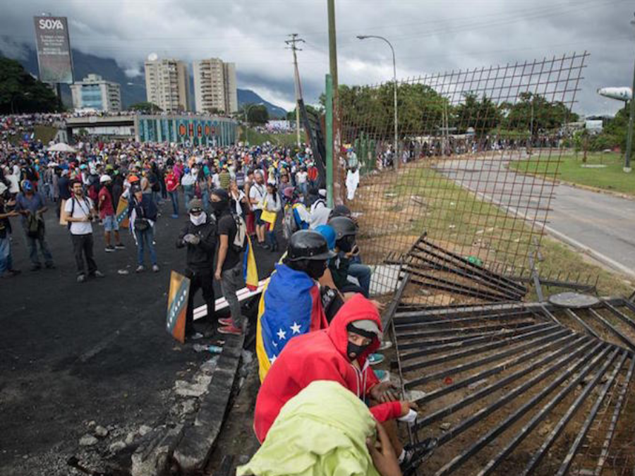 "Protesters tear down security fence at the ""Great General Francisco de Miranda"" military base. Image Credit: EFE"