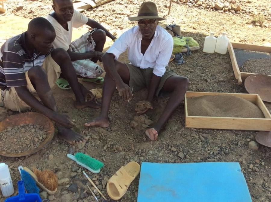 Akai Ekes and John Ekusi watch as Isaiah Nengo holds the skull. Image Credit: Isaiah Nengo
